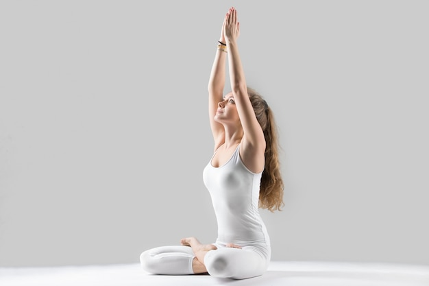 Jonge aantrekkelijke vrouw zitten in padmasana poseren, grijze studio ba