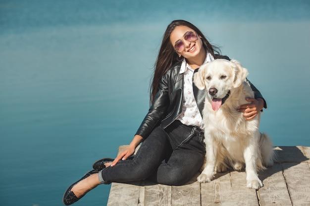 Jonge aantrekkelijke vrouw zitten op de pier met haar hond. beste vrienden buitenshuis
