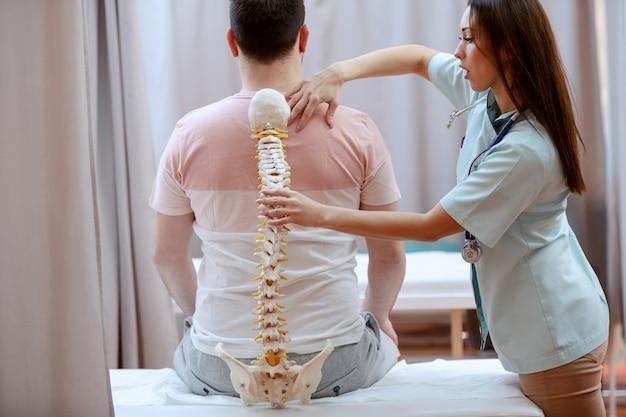 Jonge aantrekkelijke vrouwelijke arts houden wervelkolom model en truing om te realiseren waar is de pijnlijke plaats van de patiënt.