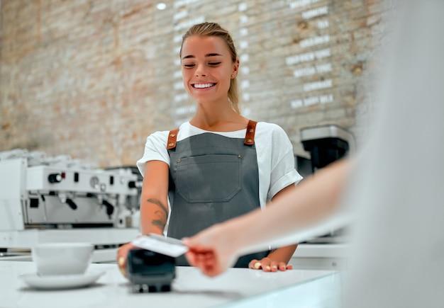 Jonge aantrekkelijke vrouwelijke barista staat aan de balie in een coffeeshop. klant betalen voor hun bestelling met een creditcard in een café.