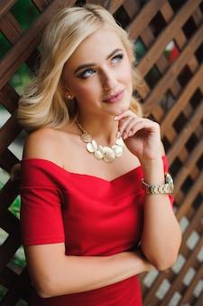 Jonge aantrekkelijke vrouwelijke blonde vrouw in rode jurk zittend op een stoel