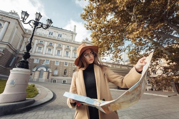 Jonge aantrekkelijke vrouwelijke reiziger wordt geleid door de stadsplattegrond. mooi meisje op zoek naar richting in de europese stad. vakantie en toerisme concept
