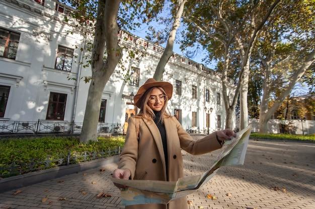 Jonge aantrekkelijke vrouwelijke reiziger wordt geleid door de stadsplattegrond. mooi meisje op zoek naar richting in de stad. vakantie en toerisme concept