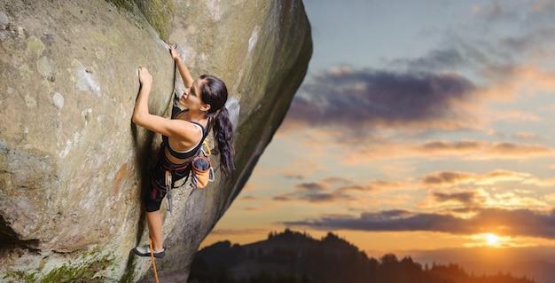 Jonge aantrekkelijke vrouwelijke rotsklimmer die uitdagingsroute op steile rotsmuur beklimt