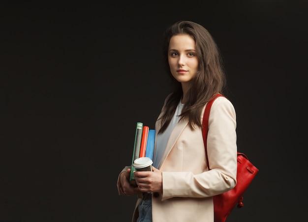 Jonge aantrekkelijke vrouwelijke student in blazer met geïsoleerde rugzak