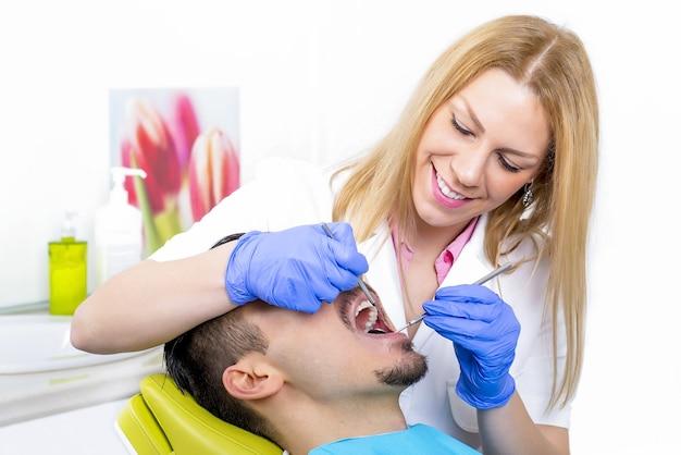 Jonge aantrekkelijke vrouwelijke tandarts die een mannelijke patiënt behandelt op haar kantoor