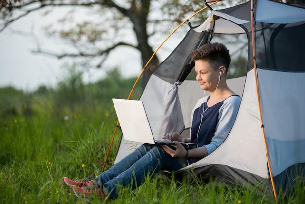 Jonge aantrekkelijke vrouwelijke zitting in een tent die in openlucht haar laptop met behulp van