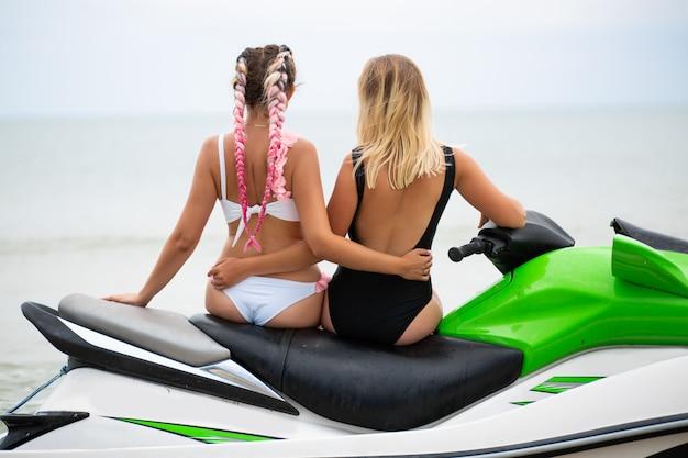 Jonge aantrekkelijke vrouwen met slank sexy lichaam in stijlvolle bikini zwembroek plezier op waterscooter, vrienden op zomervakantie, actieve sport, uitzicht vanaf achterkant