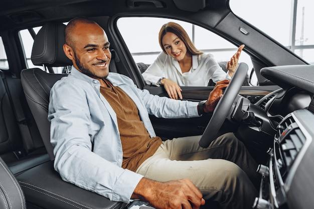 Jonge aantrekkelijke vrouwenverkoper in autotoonzaal die een auto toont aan haar mannelijke cliënt