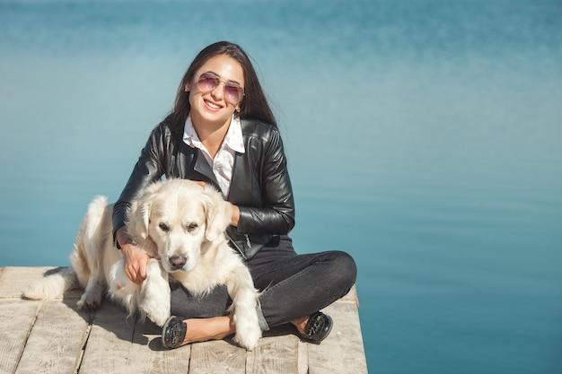 Jonge aantrekkelijke vrouwenzitting bij de pijler met haar hond. beste vrienden buitenshuis