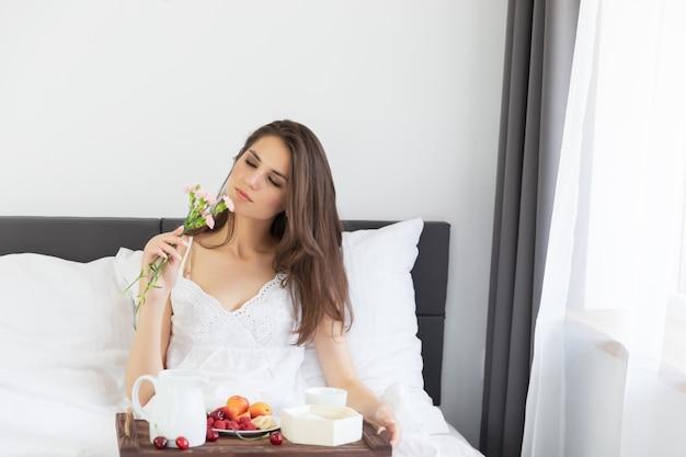 Jonge aantrekkelijke vrouwenzitting in bed met ontbijt