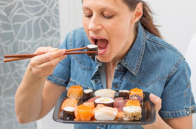 Jonge aantrekkelijke vrouwenzitting op de bank en thuis het eten van sushi