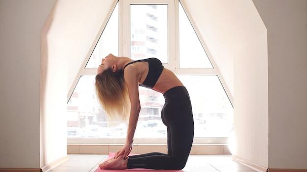 Jonge aantrekkelijke yogaleraar vrouwelijke begroeting aan het begin van het beoefenen van yoga