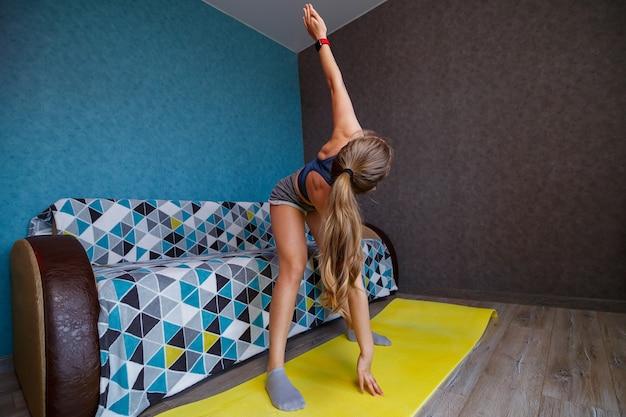 Jonge aantrekkelijke yogavrouw die yoga beoefent die utthita triconasana-oefeningen doet, uitgebreide driehoekshouding, thuis trainen, sportkleding dragen, lichaam strekken, volledige lengte binnenshuis