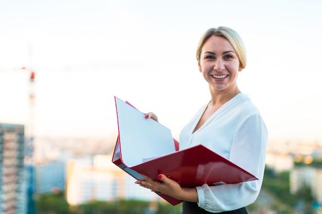Jonge aantrekkelijke zakelijke dame staan op het dak met papieren map in handen