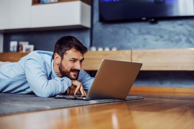 Jonge aantrekkelijke zakenman die op buik thuis op de vloer ligt en laptop met behulp van.