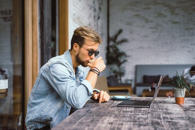 Jonge aantrekkelijke zakenman in een café werkt voor een laptop, drinkt koffie.