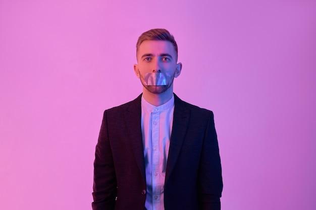 Jonge aantrekkelijke zakenman in zwart pak en wit overhemd met plakband op zijn mond die op neonroze wordt geïsoleerd