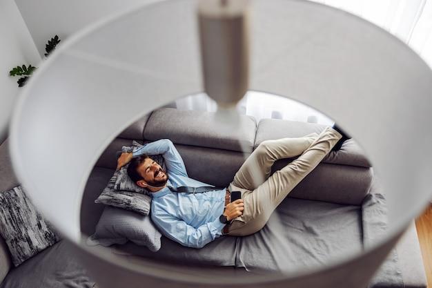 Jonge aantrekkelijke zakenman liggend op de bank thuis, ontspannen en met behulp van slimme telefoon.