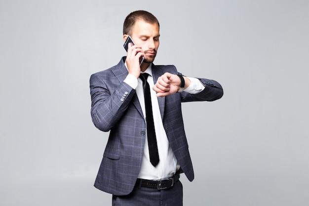 Jonge aantrekkelijke zakenman praten over een smartphone glimlacht en kijkt naar zijn horloge op een witte achtergrond