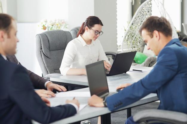 Jonge aantrekkelijke zakenvrouw die op kantoor werkt en haar strategie ontwikkelt