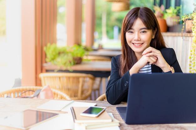 Jonge aantrekkelijke zakenvrouw in haar casual pak die op haar computer werkt op het buitenterras