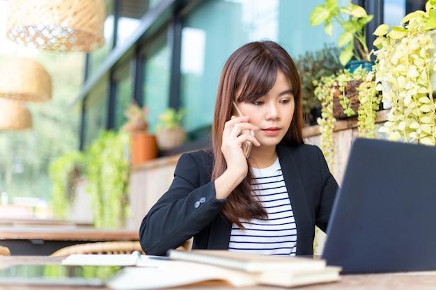 Jonge, aantrekkelijke zakenvrouw in haar casual pak die op haar telefoon praat terwijl ze op de computer werkt