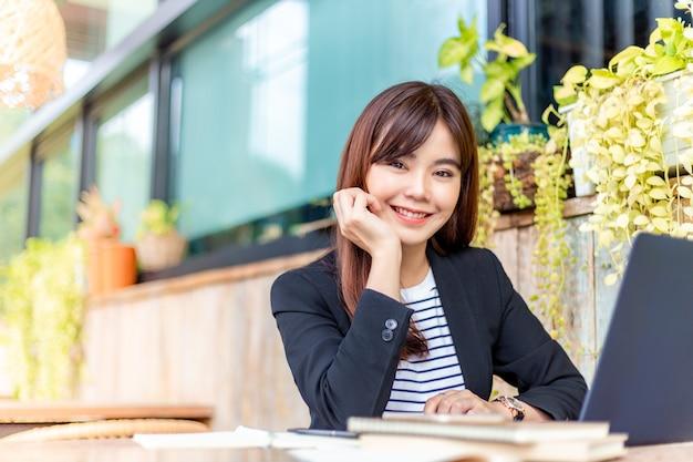 Jonge aantrekkelijke zakenvrouw in haar casual pak glimlachend naar de camera terwijl ze op haar computer werkt