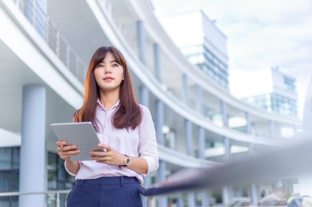 Jonge aantrekkelijke zakenvrouw in haar roze shirt die haar tabletcomputer gebruikt om sociale media te controleren
