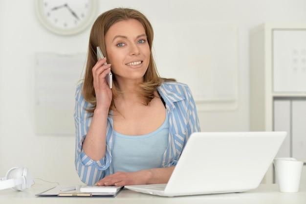 Jonge aantrekkelijke zakenvrouw met laptop die op kantoor werkt