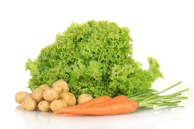 Jonge aardappelen, wortelen en sla geïsoleerd op wit