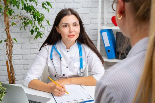 Jonge aardige vrouw arts die een gesprek met haar patiënt in het ziekenhuis heeft