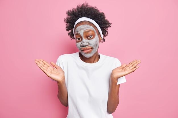 Jonge, aarzelende afro-amerikaanse vrouw spreidt handpalmen, voelt zich geen idee, past een kleimasker toe om de huid te verjongen