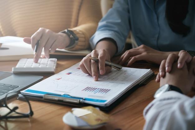 Jonge accountant marketingteam consultants en rekenmachine gebruiken om de omzetgroei op de wereldwijde werkplekmarkt te analyseren. boekhoudkundige concept