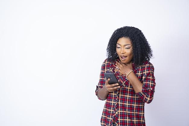 Jonge achtervrouw die haar telefoon houdt die geschokt en ongerust kijkt.
