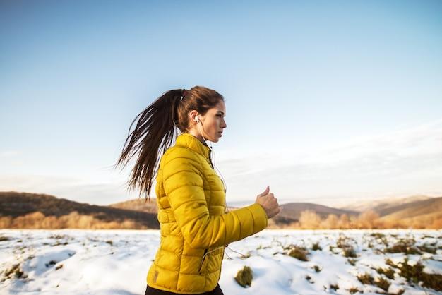 Jonge actieve atletische meisjesjogging in de wintersportkleding op sneeuw de winterweg met oortelefoons in de zonnige ochtend.