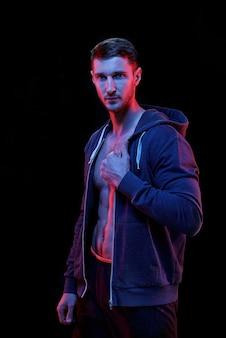 Jonge actieve man in hoodie en korte broek naar je kijken terwijl je tegen een zwarte muur staat