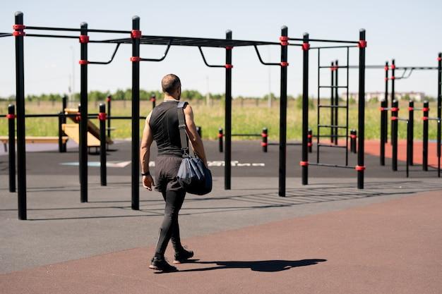 Jonge actieve man in sportkleding op weg naar sportfaciliteiten terwijl hij buiten gaat trainen