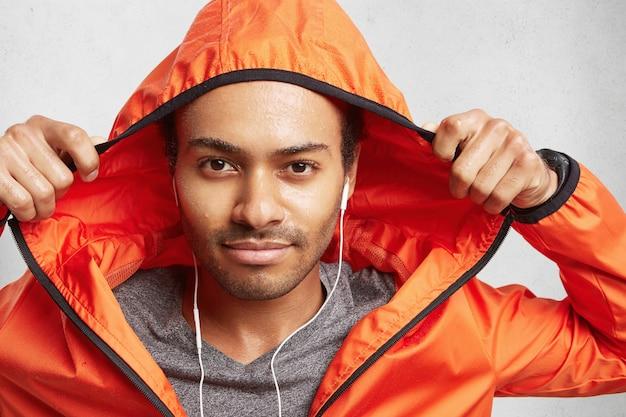 Jonge, actieve man van gemengd ras met donkere huid en stoppels, die nat is na sporten bij regenachtig weer