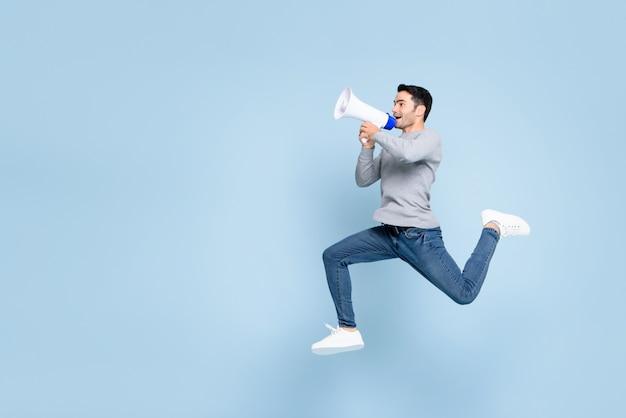 Jonge actieve mens die en op megafoon springt schreeuwt die met exemplaarruimte wordt geïsoleerd