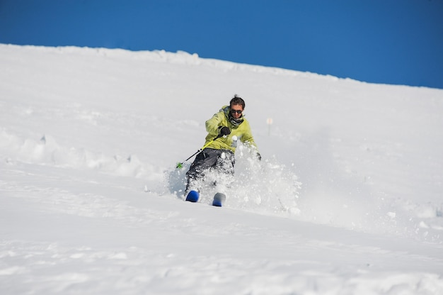Jonge actieve skiër in felgele sportkleding rijden de bergen af