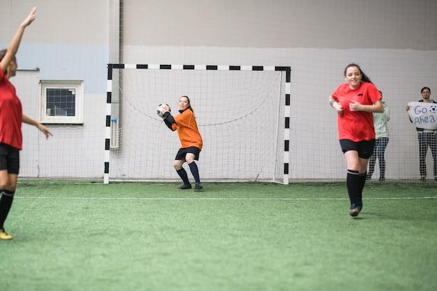 Jonge actieve sportvrouw gaat voetbal gooien naar een andere speler van haar team terwijl ze tijdens het spel in poorten staat