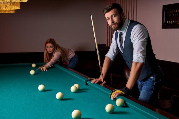 Jonge actieve vrienden spelen na het werk biljart in de bar, hebben rust en vrije tijd en bereiden zich voor om poolballen te schieten