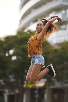 Jonge actieve vrouw die hoogspringen in de straat uitvoert