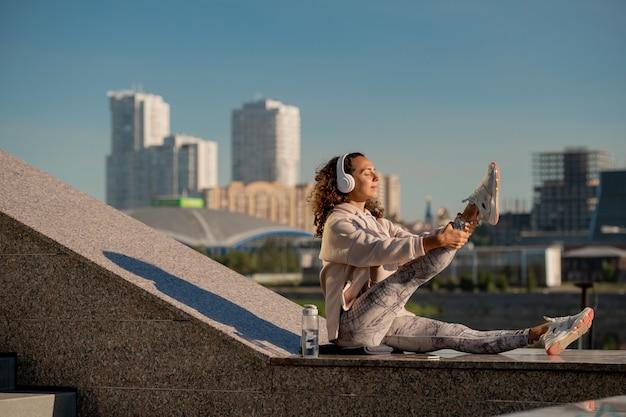 Jonge actieve vrouw in sportkleding luisteren naar muziek of audiotraining in koptelefoon tijdens het oefenen op marmeren structuur buitenshuis
