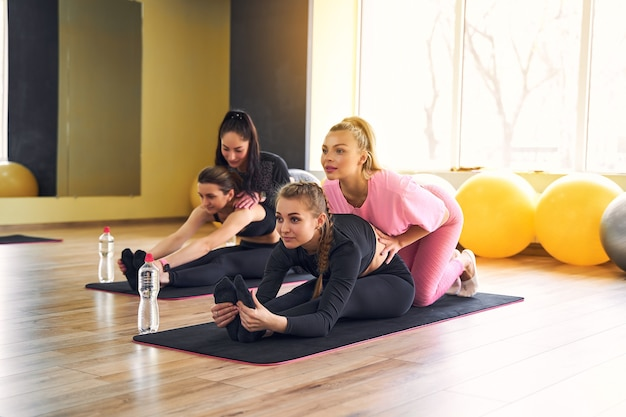 Jonge actieve vrouwen met een slank lichaam die rekoefening doen om fitte lichaamsflexibiliteit op yogamat te houden