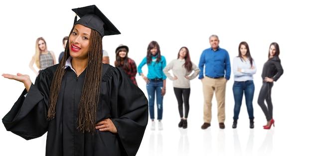 Jonge afgestudeerd zwarte vrouw die vlechten draagt die iets met handen houden, die een product tonen