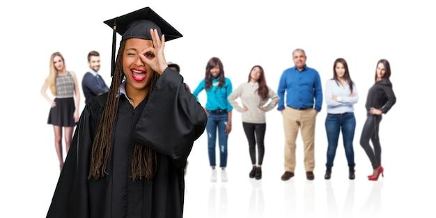 Jonge afgestudeerd zwarte vrouw dragen vlechten vrolijk en vol vertrouwen doen ok gebaar