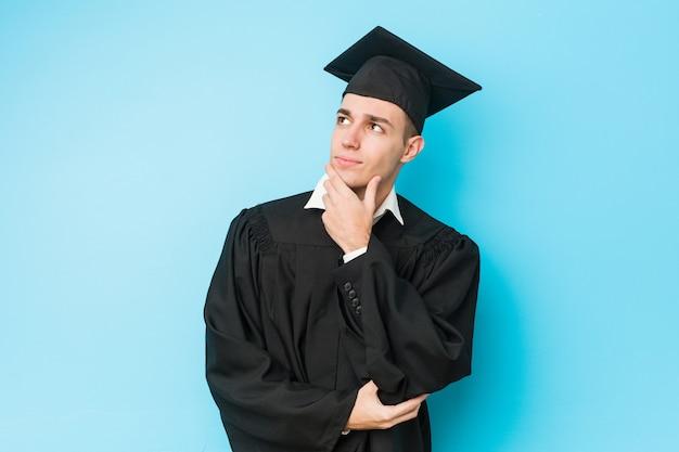 Jonge afgestudeerde man opzij met twijfelachtige en sceptische uitdrukking