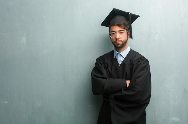Jonge afgestudeerde man tegen een grunge muur met een kopie ruimte overschrijding van zijn armen, serieus en opleggen, gevoel vertrouwen en macht tonen